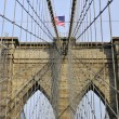 Upward image of Brooklyn Bridge in New York at sunny day - Stock Photo