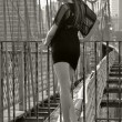 Fashion model posing sexy in short black dress on Brooklyn Bridge in New York — Stock Photo