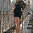 Fashion model posing sexy in short black dress on Brooklyn Bridge in New York - Foto Stock