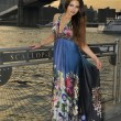 Fashion model posing in long blue dress in front of Brooklyn Bridge in New York City - Photo