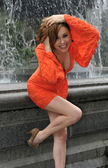 Fashion model posing in short red dress in front of fountain in New York City park — Stock Photo