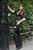 Moda modelu pozowanie w czarny płaszcz i policji kapelusz przed metal brama w new york city park — Zdjęcie stockowe
