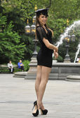 Fashion model posing in short black dress and NYPD police hat in front of fountain in New York City park — Stock Photo