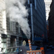 Steam venting from the street, utility pipe hot steam to building for heating, south street sea port, lower Manhattan, New york - Stock Photo