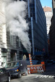 Steam venting from the street, utility pipe hot steam to building for heating, south street sea port, lower Manhattan, New york — Stock Photo