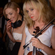 MIAMI - JULY 15: Violinist Caitlin Moe and DJ Mia Moretti perform at the Wildfox Swim 2012 presentation at penthouse of Railegh hotel during Mercedes-Benz Swim Fashion Week - Stock Photo