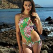Model in tropical swimsuit posing at oceanside location — Stock Photo