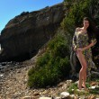 Model posing in transparent dress at oceanside - Stock fotografie