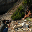 Photo video crew on location set with bikini model - Stock Photo