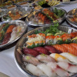 Sushi, sashimi, rolls on trays and cold snacks - Stockfoto
