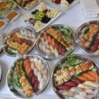 Sushi, sashimi, rolls on trays and cold snacks -  