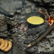 Fried eggs on fire at iron fried pan with grilled sausages - Stock Photo
