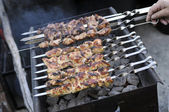 Meat on skewers being flame grilled on a bbq — Stock Photo