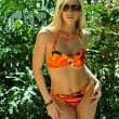 Pretty blond girl wearing bikini looking straight to the camera in tropical garden — Stock Photo