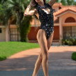 Fashion model in designers swimsuit posing in front of house — Stock Photo