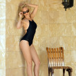 Blond woman in black onepiece swimsuit — Stock Photo
