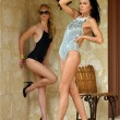 Two fashion models in designers swimsuit posing in front of house - Stock Photo