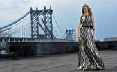 Fashion model posing sexy, wearing long evening dress on rooftop location with metal bridge construction on background — Stock Photo