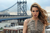 Close up portrait of fashion model with full sexy hair and red lips posing on rooftop location with metal bridge construction on background — Stock Photo