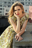 Portrait of fashion model posing sexy, wearing long evening dress on rooftop location — Stock Photo