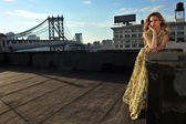 Fashion model posing sexy, wearing long evening dress on rooftop location — Stock Photo
