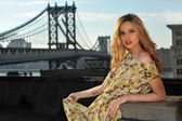 Portrait of fashion model posing sexy, wearing long evening dress on rooftop location with metal bridge construction on background — Stock Photo
