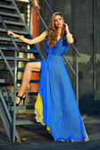 Fashion model posing sexy, wearing long blue evening dress on rooftop location — Stock Photo