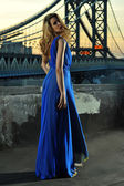 Fashion model posing sexy, wearing long blue evening dress on rooftop location with metal bridge construction on background — Photo