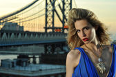 Close up portrait of fashion model with full sexy hair and red lips posing on rooftop location — Stock Photo