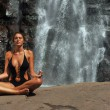 Beautiful girl wearing black one piece swimsuit meditating in lotus yoga  — Stock Photo