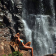 Beautiful slim fitness model posing sexy in front of waterfalls — Stock fotografie