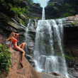 Beautiful slim fitness model posing sexy in front of waterfalls — Lizenzfreies Foto
