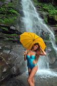 Girl posing in front of waterfalls with yellow umbrella — Stock Photo