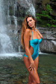 Beautiful slim fitness model posing sexy in front of waterfalls — Stock Photo