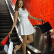Young sexy woman with shopping bags at fashion mall escalator — Stock Photo
