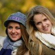 Two beautiful young girls posing in a autumnal park — Stock Photo