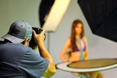 Photographer shooting model in the studio — Stock Photo