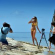 Photographer shooting model on the beach — Stock Photo #38019469