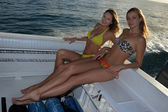 Two bikini models sitting on cockpit of motor boat — Stock Photo