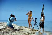 Photographer shooting model on the beach — Stock Photo