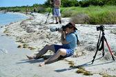 Fotograf sitzen am Strand — Stockfoto