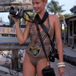 Model holding three professional photo cameras at tropical location — Stock Photo #38274537