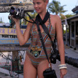 Stock Photo: Model holding three professional photo cameras at tropical location
