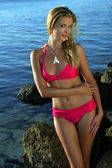Bikini model posing on rocks — Stock Photo