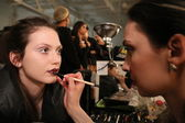 Make-up artist applying lipstick to model face — Stock Photo