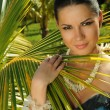 Brunette standing in front of palm tree — Stock Photo #46706667