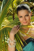 Brunette standing in front of palm tree — Stock Photo