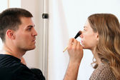 Makeup artist applying makeup to model — Stock Photo