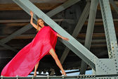 Fashion model posing inside of metal bridge — Stock Photo