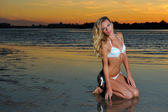 Woman in bikini on the beach at sunset — Stock Photo